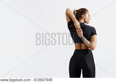 Rear View Of Healthy And Fit Sports Woman Stretching Arms Before Exercising, Looking Away Determined
