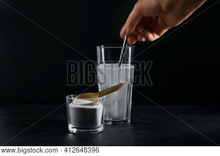 Glass With Collagen Dissolved In Water And Collagen Protein Powder On Black Background. Woman's Hand