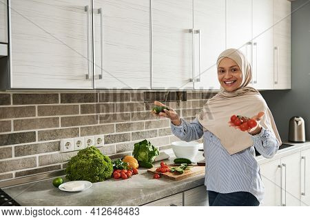 Beautiful Muslim Woman In Hijab Cute Smiles With Toothy Smile To Camera While Preparing A Healthy Ve