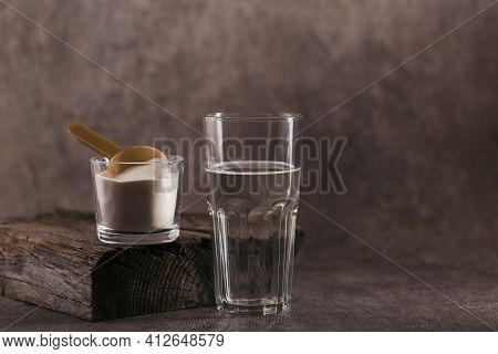 Glass With Collagen Dissolved In Water And Collagen Protein Powder On Brown Background. Healthy Life
