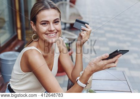 Smiling Woman Holding Phone And Credit Card Outdoors In Cafe. A Beautiful Model Looks At The Camera