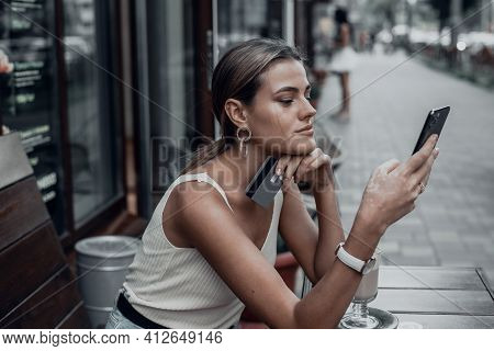 Young Smiling Woman Shopping Online Using Phone Outdoors In Cafe. A Beautiful Model Looks At The Pho