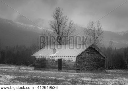 A Black And White Photo Of An Old Shed In Winter In North Idaho.