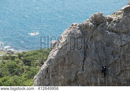 High Cliff And Small Figure Of Rock Climber. Sea Is Behind. Extreme Sport. Spring, Cremea, Breathtak
