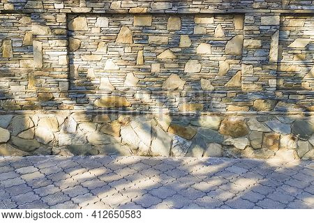 Close-up And Selective Focus Of Stone Fence Made Of Sandstone Laid Out With Mosaics And Asphalt Tile