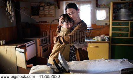 Portrait Of Sad Poor Mature Mother Hugging Small Daughter Indoors At Home, Poverty Concept.