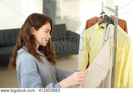 Girl Chooses Clothes At Home Wardrobe. Woman Chooses Things On Shoulders In Dressing Room Or In Shop