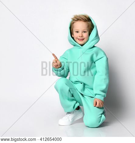 Blond Boy In A Tracksuit And A Hood On His Head Sits On A Gray Background. A Child In A Warm Turquoi