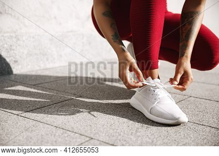 Cropped View Of Female Runner Tie Shoelaces On Outdoor Jogging Exercises. Sportswoman Tying Shoes Be