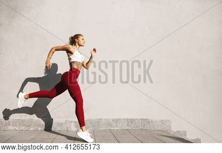 Strong Woman In Sportswear Running And Exercising Outdoors. Caucasian Female Doing Running Workout I
