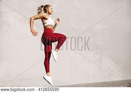Fitness Woman Doing Cardio Interval Training Outdoors. Side View Of Athletic Female Model Jumping By