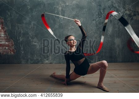 Young Girl Professional Gymnast Woman Rhythmic Gymnastics With Ribbon At Studio