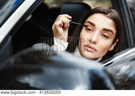 Businesswoman Applying Mascara And Looking At Rear-view Mirror, Put On Makeup On Her Way To Business
