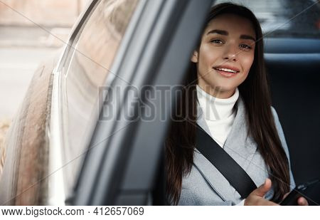 Elegant Businesswoman Sitting On Backseat Of Her Car With Seatbelt, Using Mobile Phone. Smiling Woma