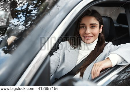 Happy Elegant Woman Sitting In Car With Fastened Seatbelt, Driving At Work. Female Driver Smiling At