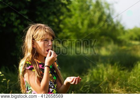 Cute Child Girl With Blonde Long Hairs Is Eating Strawberry. Bright Clothes. She Is Standing On The