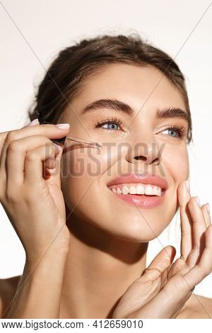Beauty And Skincare Concept. Smiling Woman Applying Argan Oil Essential, Balance Skin Tone With Vita