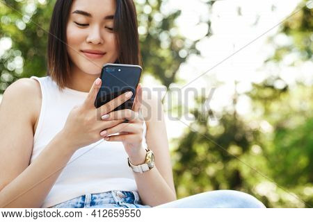 Close-up Of Young Asian Woman Using Mobile Phone While Sitting In Park. Girl Smiling And Reading Tex