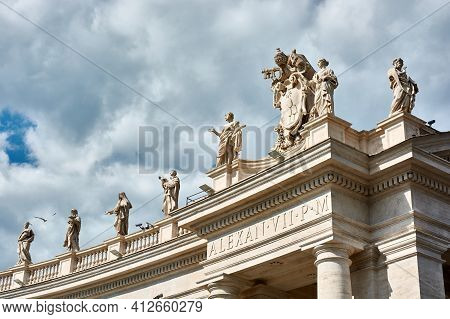 View Of Sculptures On Top Of The Tuscan Colonnades And Blue Cloudy Sky At St. Peter's Square In The