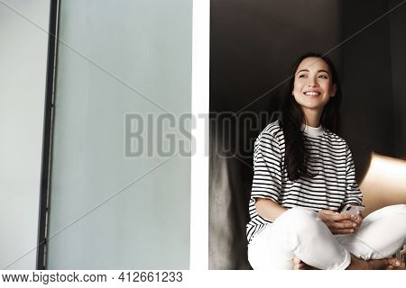 Asian Woman Resting At Home With Mobile Phone. Girl Sitting In Her Room And Using Smartphone