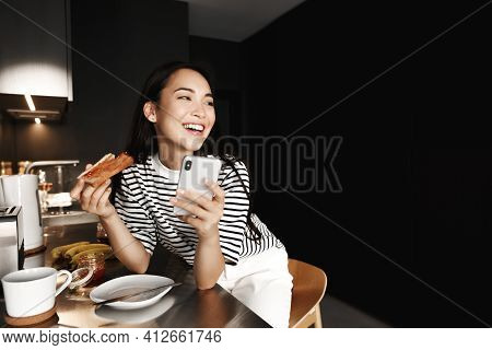 Lifestyle. Beautiful Asian Woman Resting At Home, Eating Breakfast Toast In Kitchen And Using Mobile