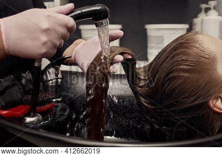 Close-up Of The Water Washing The Paint Off The Client Hair. Beauty Salon.