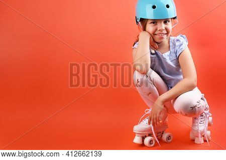 A Small Child With Roller Skates And A Blue Helmet Demonstrates Positive Emotions. A Girl Of 7 Years