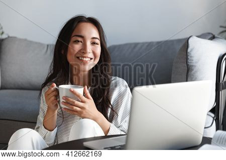 Home, Lifestyle And Leisure Concept. Beautiful Asian Girl Smiling And Drinking Tea While Watching On