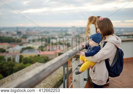 Cute Teenage Girl Holding Her Baby Brother While Enjoying A View Of Vilnius City From The Gediminas