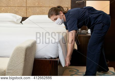 Housemaid Tucking The Sheet In The Bed In The Hotel Room
