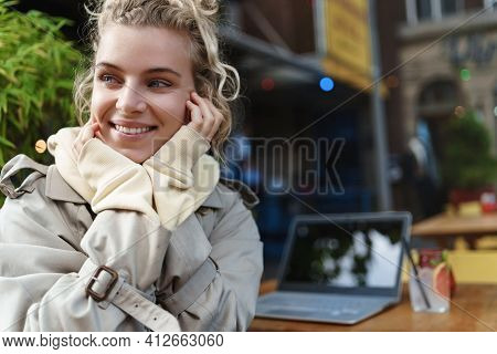 Rear View Close-up Of Happy Smiling Woman Enjoying Watching At Street Passersby While Sitting Outdoo