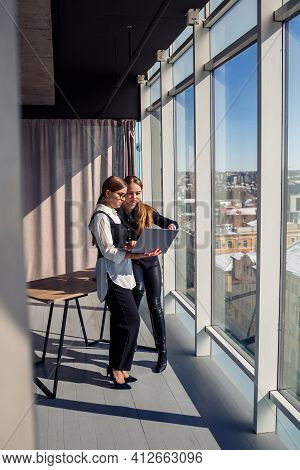Two Successful Female Architects Are Talking About A Joint Project While Standing At The Window With
