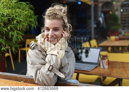 Rear View Of Beautiful Happy Woman Smiling At Camera, Sitting Outdoor Cafe Table With Laptop And Coc