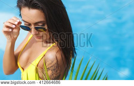 Sexy Brunette Woman With Golden Tan And Tattoo, Wearing Bikini With Sunglasses, Relaxing At Hotel Po