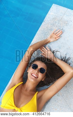 Tourism And Spa. Top View Of Sexy Brunette Woman In Bikini And Sunglasses, Lying Near Poolside. Fema