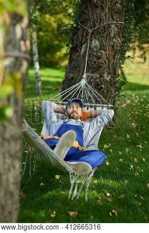 Peaceful Young Workman Wearing Uniform Taking A Break, Lying In A Hammock Outdoors With Eyes Closed