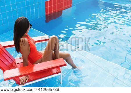 Rear View Of Sexy Brunette In Red Swimsuit, Sit Lifeguard Chair At Look Swimming Pool, Soaking Feet