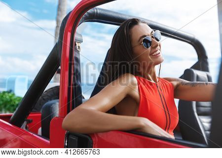 Smiling Attractive Tanned Woman In Red Swimsuit Driving Car. Sexy Female Model Lean Hand Door, Drive