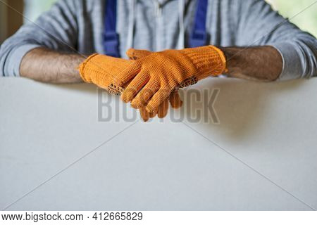 Close Up Shot Of Hands Of Male Builder Wearing Protective Gloves Holding Drywall While Working On Ho