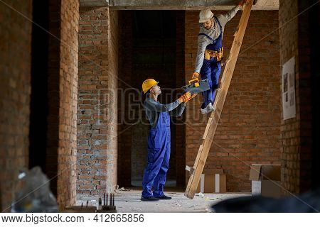 Assistance. Full Length Shot Of Young Workman In Blue Overalls And Hard Hat Giving Toolbox To His Co