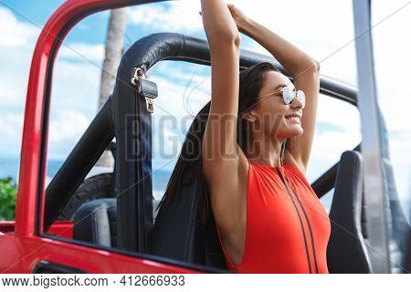 Sexy Tanned Woman In Sunglasses And Red Bikini Lifting Hands Up In Car, Driving Lifeguard Jeep Acros