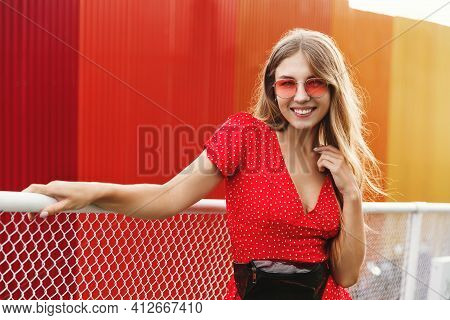 Portrait Of Happy Smiling Woman Standing Near Red City Wall On Sunny Summer Or Spring Day Outside, C