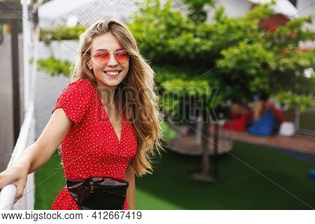 Outdoor Portrait Of Beautiful Blonde Woman Having Fun On City Streets Of Tropical City, Standing In
