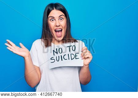 Young beautiful woman asking for psychical problem holding paper with not to suicide message celebrating achievement with happy smile and winner expression with raised hand