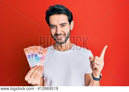 Young hispanic man holding swiss franc banknotes smiling happy pointing with hand and finger to the side
