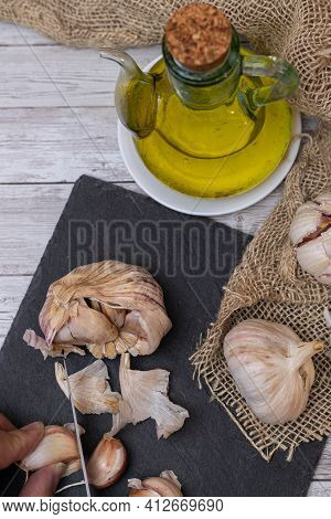 Person Cutting Garlic Cloves On A Table With Several Garlic Bulbs And Oil To Prepare The Aromatic An