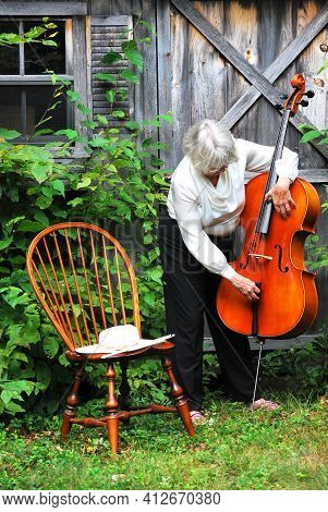 Mature Female Senior With Her Cello Outside.