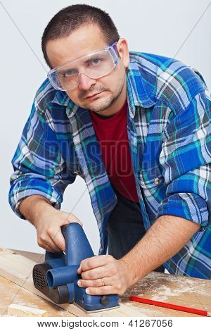 Man Working Wood With An Electric Planer