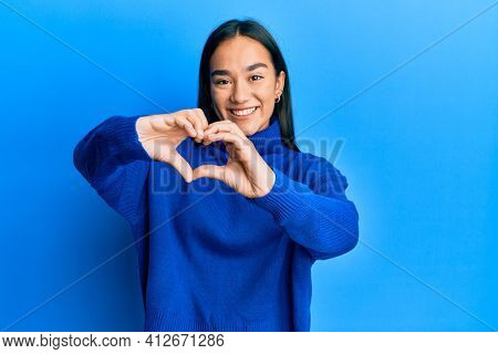 Young asian woman wearing casual winter sweater smiling in love doing heart symbol shape with hands. romantic concept.