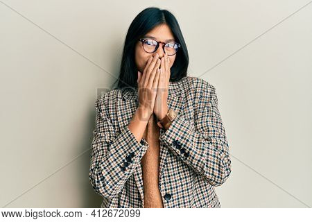 Young chinese woman wearing business style and glasses laughing and embarrassed giggle covering mouth with hands, gossip and scandal concept